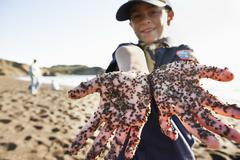 Mixed race boy showing dirty hands on beach Stock Photos