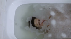 Pensive man reflects his problems immersed in the bath tub - bathtube - dive Stock Footage