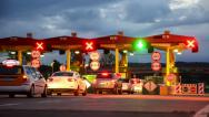 Stock Video Footage of highway car paytoll at sunrise, night lights and autos passing through toll b