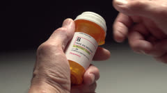 Man unable to open a pill bottle - stock footage