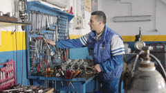 Auto mechanic taking wrench for repairing a motor of a car - dolly Stock Footage