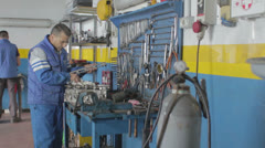Auto mechanic reassembles and  cleans  a motor after repair - dolly Stock Footage