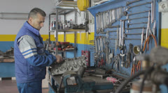 Auto mechanic repairing a part of a car engine - dolly - stock footage
