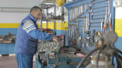 Auto mechanic repairing a part of a car - dolly - stock footage