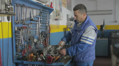 Auto mechanic repairing a part of a car - dolly Stock Footage