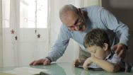 Stock Video Footage of child playing with a video game together his grandfather