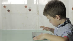 Beautiful child plays with the tablet Stock Footage