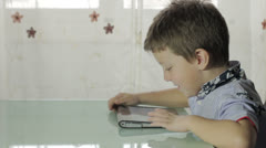 Beautiful child uses a tablet and looks at the camera Stock Footage