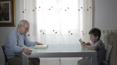 The past and the future, grandfather reading a book and child uses tablet Stock Footage
