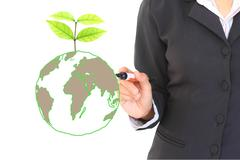 Businessman holding green planet with tree growing Stock Photos