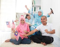 Malaysian family celebrating while watching television over a tournament , so Stock Photos