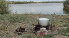 Аt the stake on the bank of the river boiled fish soup Stock Footage