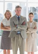 Stock Photo of Three serious business people standing together