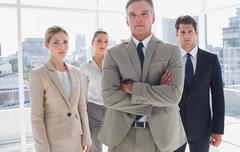 Stock Photo of Boss standing with his arms folded with colleagues behind