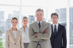 Stock Photo of Boss with his arms folded standing with smiling colleagues behind