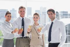Smiling team of business people honoring a success with champagne - stock photo
