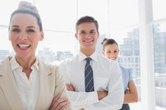 Stock Photo of Smiling attractive businesswoman standing with arms crossed