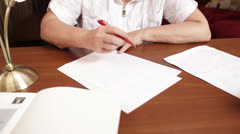 Middle-aged woman writing at the table Stock Footage