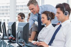 Smiling manager helping call centre agent - stock photo