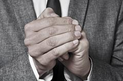 man in suit rubbing his hands - stock photo