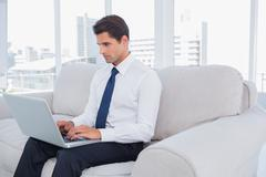 Stock Photo of Businessman using laptop on a couch