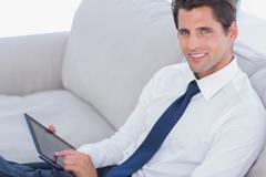Stock Photo of Smiling businessman using digital tablet