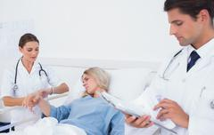 Doctor taking pulse of a patient - stock photo