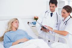 Hospitalized woman and doctors - stock photo