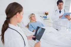 Doctors with xray and digital tablet - stock photo