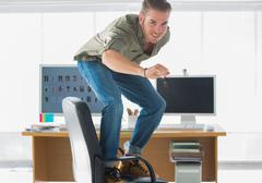 Smiling man surfing his office chair Stock Photos