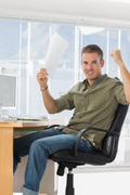Cheerful creative business employee raising arms - stock photo