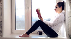Girl reads the book wearing spectacles sitting on a window sill Stock Footage