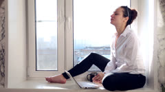 Girl working at the laptop sitting on a window Stock Footage
