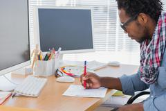 Handsome designer drawing something with a red pencil - stock photo