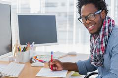 Smiling designer drawing something with a red pencil - stock photo