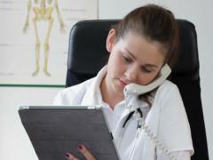 Female doctor talking on landline phone and working on tablet computer NTSC Stock Footage