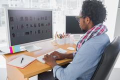 Stock Photo of Handsome photo editor working on computer