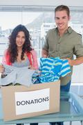 Stock Photo of Volunteers taking out clothes from a donation box