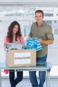 Stock Photo of Smiling volunteers taking out clothes from a donation box