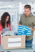 Stock Photo of Serious volunteers taking out clothes from a donation box