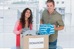 Stock Photo of Smiling volunteers taking out clothes from donations box