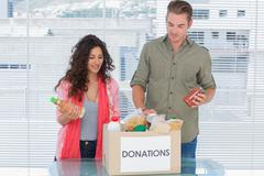 Volunteers taking out food from donations box Stock Photos