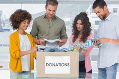 Stock Photo of Happy team of volunteers taking out clothes from a donation box