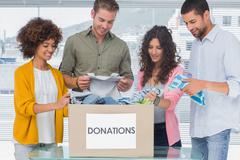 Stock Photo of Young team of volunteers taking out clothes from a donation box