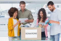 Stock Photo of Volunteers using tablet and taking out clothes from a donation box