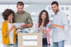 Stock Photo of Smiling volunteers using tablet and taking out clothes from donations
