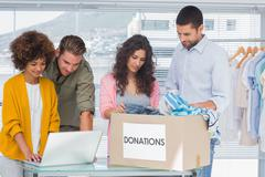 Volunteers using a laptop and taking clothes from charity box Stock Photos