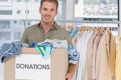 Stock Photo of Handsome man holding donation box