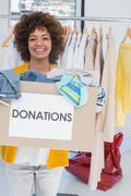 Stock Photo of Young volunteer holding clothes donation box