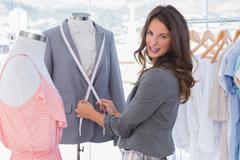 Stock Photo of Attractive fashion designer measuring blazer
